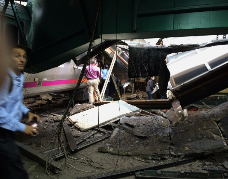 In a photo provided by William Sun, people examine the wreckage of a New Jersey Transit commuter train that crashed into the train station during the morning rush hour in Hoboken,, N.J., Thursday, Sept. 29, 2016.