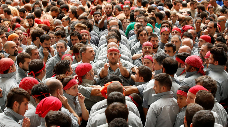 """Image: Castellers de Sants start to form a human tower called \""""castell\"""" during a biannual competition in Tarragona city"""