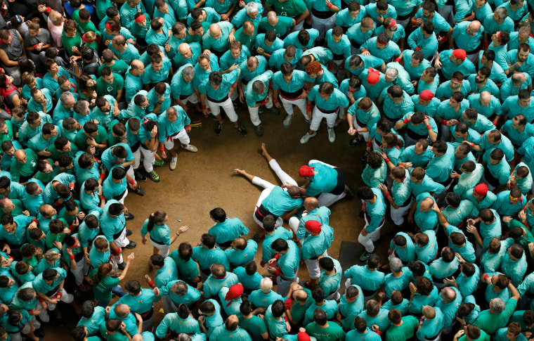 Image: A Casteller de Vilafranca is attended to after falling down from a Castell during a biannual competition in Tarragona city