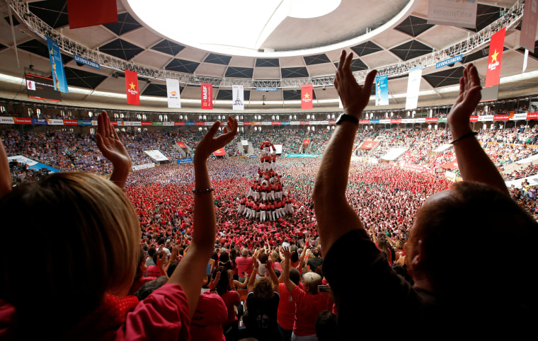 """Image: Colla Vella Xiquets de Valls form a human tower called \""""castell\"""", while supporters celebrate, during a biannual competition in Tarragona"""