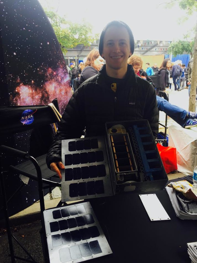 Seth Dennis shows off a prototype of a satellite.