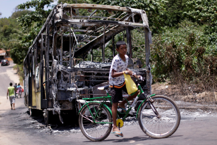 Image: A bus is pictured after it was set on fire during violent disturbances ahead of municipal elections in Sao Luis