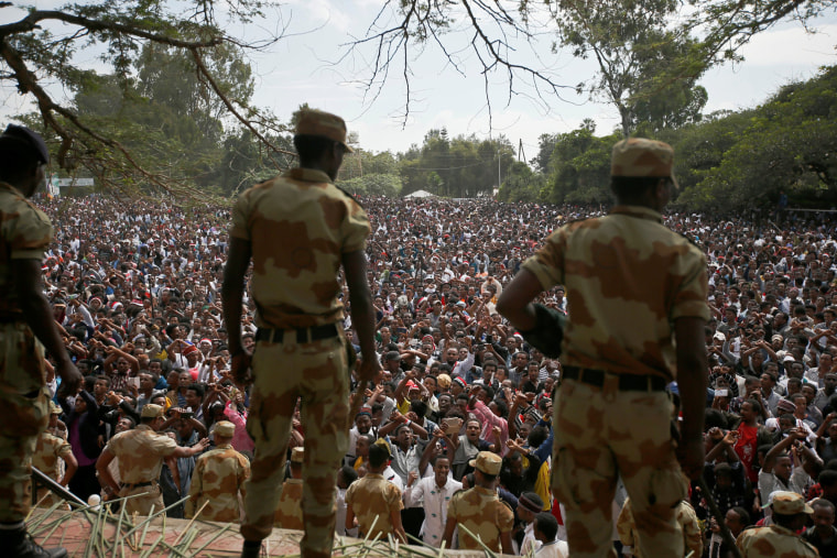 Image: Police officers watch as demonstrators chant slogans while flashing the Oromo protest gesture during Irreecha, the thanksgiving festival of the Oromo people, in Bishoftu town, Oromia region, Ethiopia