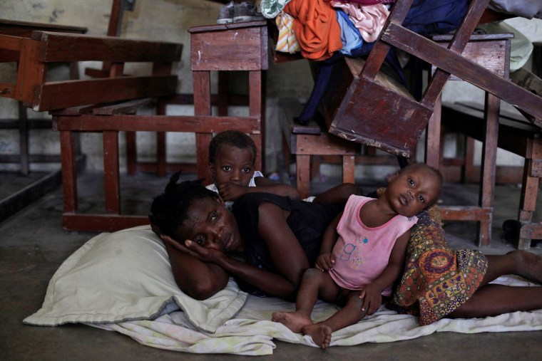 Image: A woman with two of her children rest on the floor at the shelter set up in the Lycee Philippe Guerrier ahead of Hurricane Matthew in Les Cayes