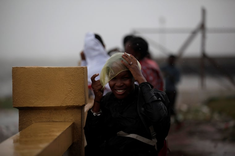 Image: A woman adjusts a plastic cap ahead of Hurricane Matthew in Les Cayes, Haiti