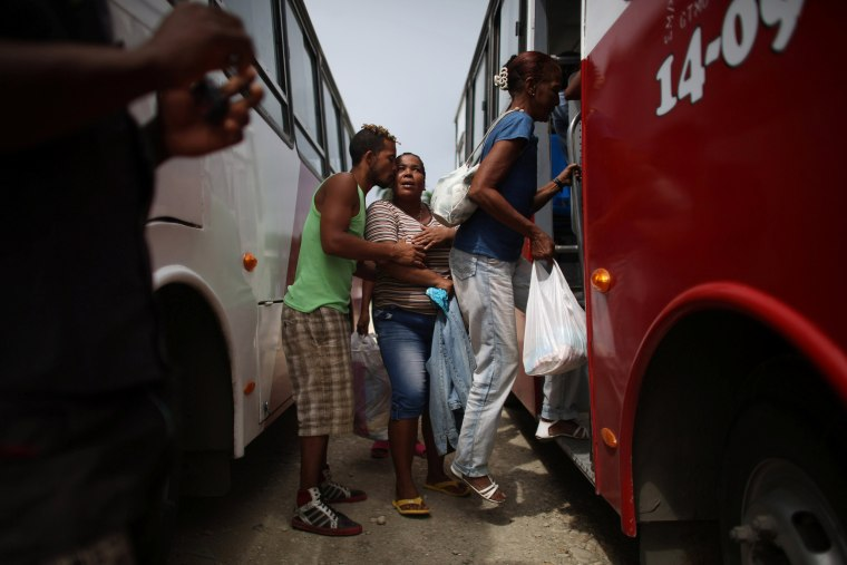 Image: A man says goodbye to relatives as they get in a bus to be evacuated ahead of the arrival of Hurricane Matthew in Secilia