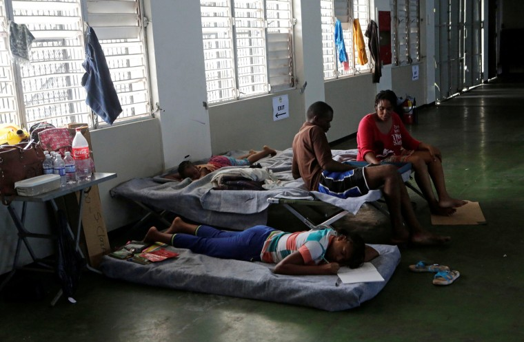 Image: People who were evacuated from their homes are seen in a room at a soccer stadium being used as a shelter while Hurricane Matthew approaches Kingston