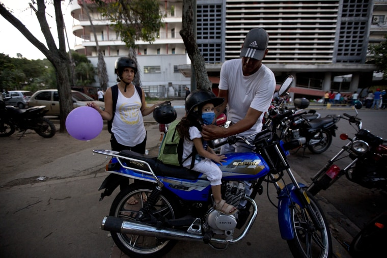 In this Sept. 19, 2016 photo, Maykol Pacheco, places a helmet on his daughter Ashley as they prepare to ride away from the University Hospital in Caracas, Venezuela.
