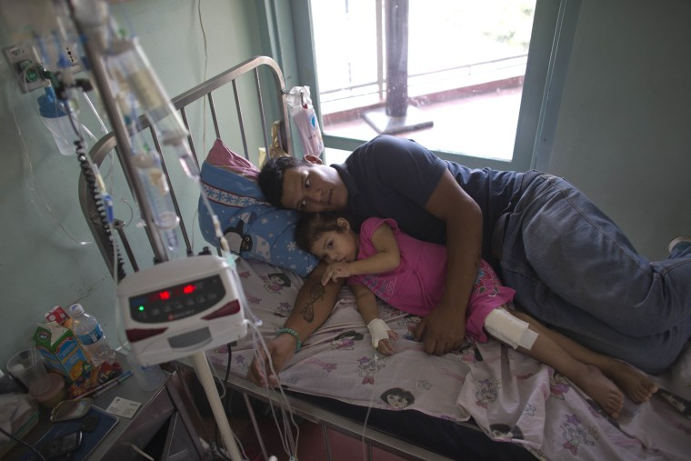 In this Aug. 11, 2016 photo, 3-year-old Ashely Pacheco rests with her father Maykol Pacheco in her hospital bed at the University Hospital in Caracas, Venezuela.