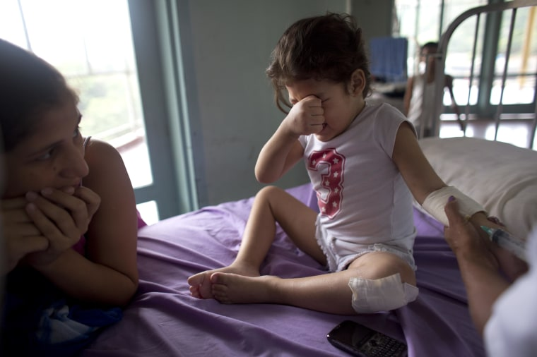In this Aug. 24, 2016 photo, Ashley Pacheco, 3, cries as she receives an injection as her mother Oriana watches at the University Hospital in Caracas, Venezuela.