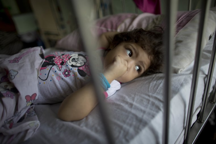 In this Aug. 16, 2016 photo, 3-year-old Ashley Pacheco sucks on her thumb as she rests in a hospital bed during her two-month stay at University Hospital in Caracas, Venezuela.