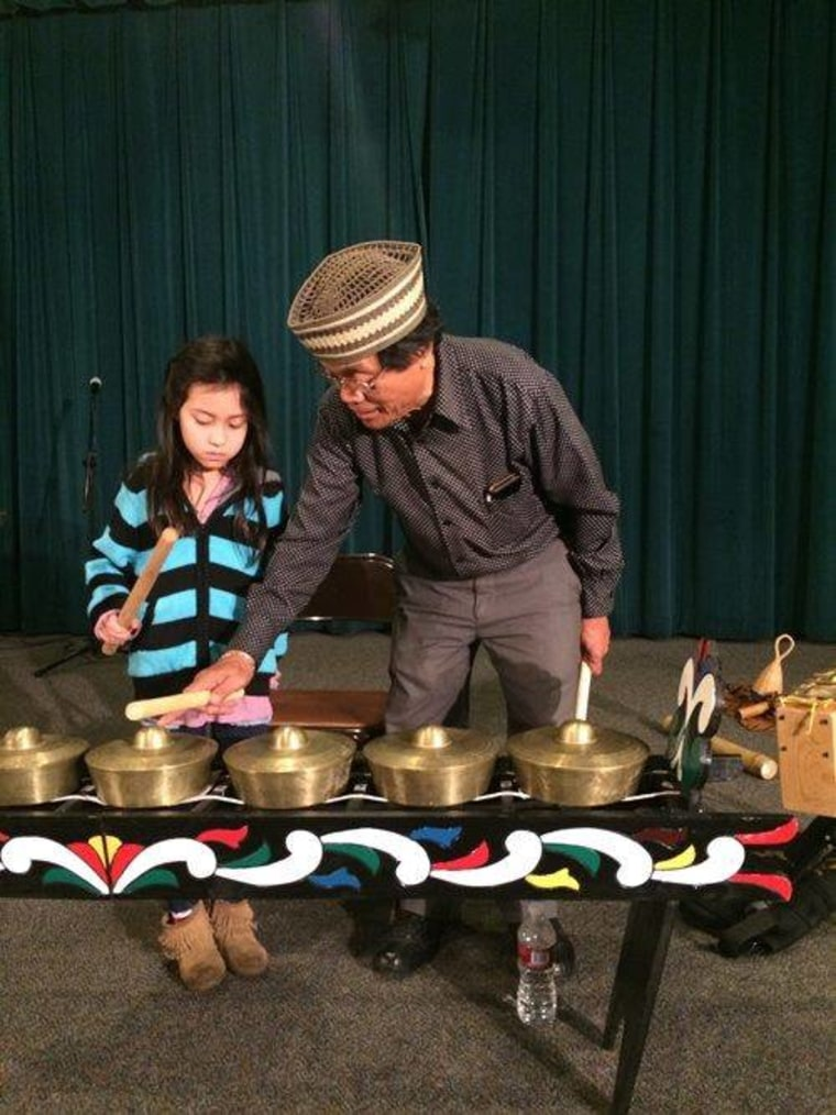 Kalanduyang teaching a child how to play the kulintang gongs during a demonstration.