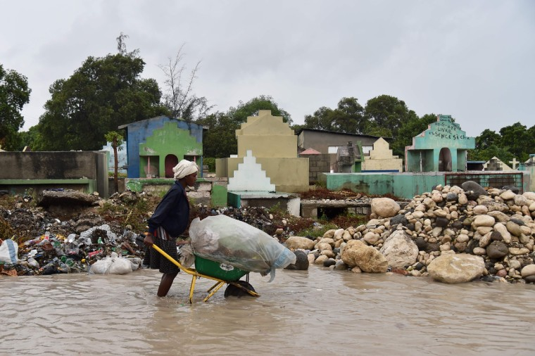 Image: A woman pushes a wheelbarrow while walking in a partially flooded street in Port-au-Prince
