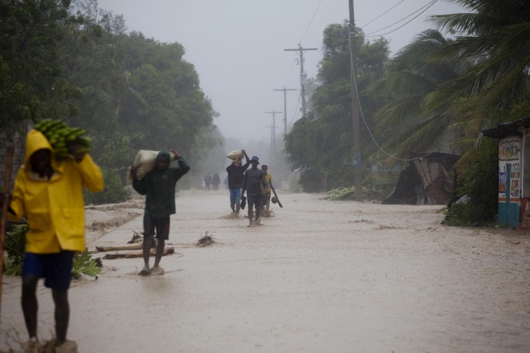 Image: Residents walk in flooded streets as they return to their homes in Leogane, Haiti