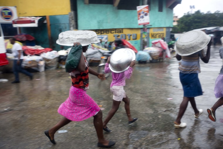 Image: Women cover their heads with pans as they walk in a light rain brought by Hurricane Matthew