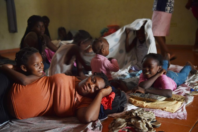 Image: A Haitian family takes shelter after their home was damaged by Hurricane Matthew