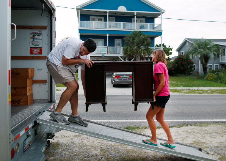 Image: Legge helps his sister-law remove furniture from the lower level of her beachfront home in anticipation of Hurricane Matthew in Garden City Beach