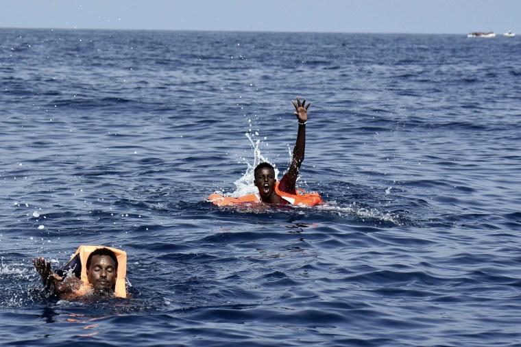 Image: Migrants gesture towards members of Proactiva Open Arms NGO