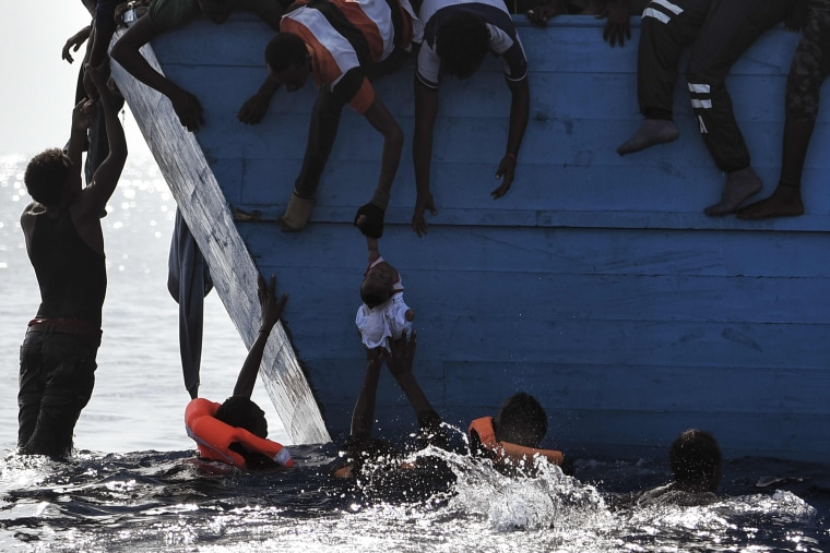 Image: Migrants try to pull a child out of the water as they wait to be rescued by members of Proactiva Open Arms NGO