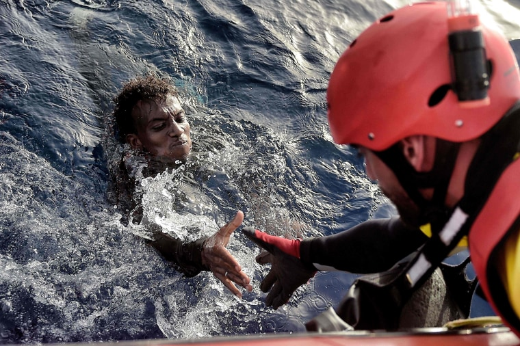 Image: A migrant is rescued from the mediteranean sea by a member of Proactiva Open Arms NGO