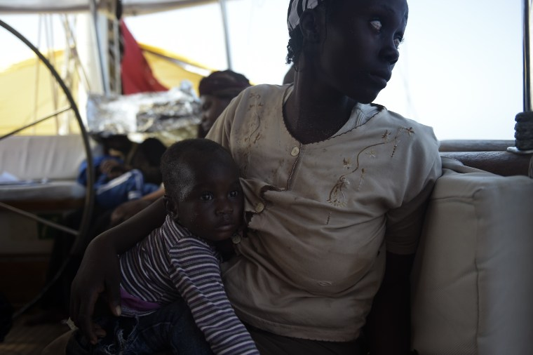 Image: A mother holds her child after migrants were rescued by members of Proactiva Open Arms NGO