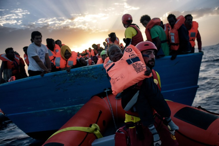 Image: A child from African origin is rescued from a distressed vessel by a member of Proactiva Open Arms NGO