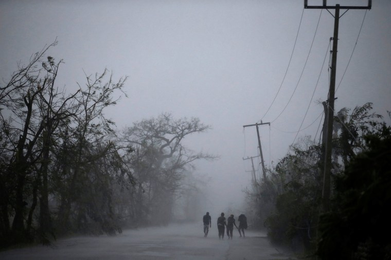 Image: People walk on the road as rain falls during Hurricane Matthew in Les Cayes, Haiti