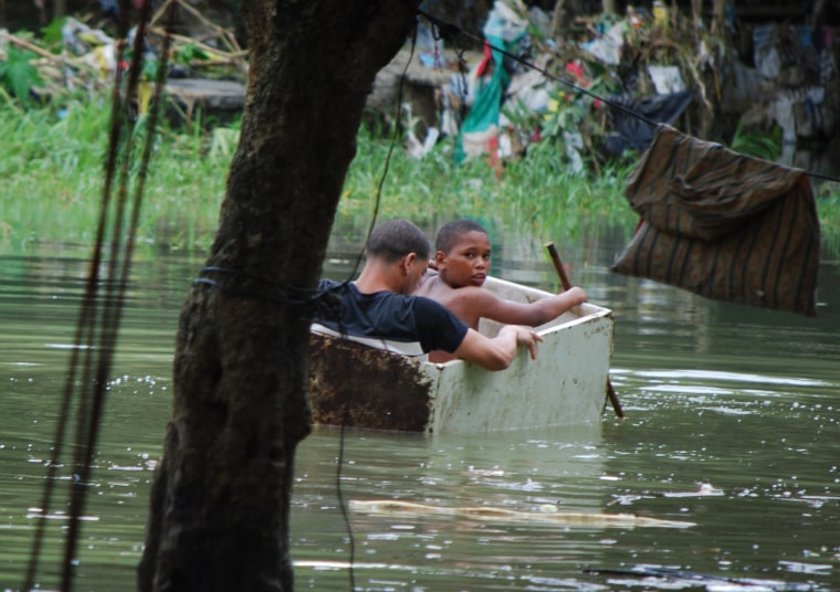 Image: Two boys float in an old wooden box in an area flooded by heavy rains caused by Hurricane Matthew