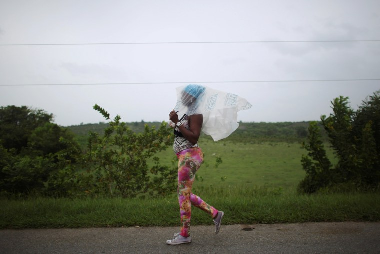 Image: Naomi Rivera, 41, shields herself from the rain ahead of the arrival of Hurricane Matthew in Guantanamo, Cuba