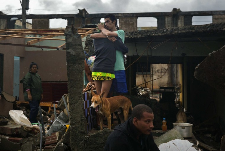 Image: A couple embrace in the remains of their home that was destroyed by Hurricane Matthew