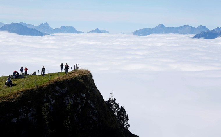 Image: Tourists walk in the sun on the Niederhorn mountain near Interlaken