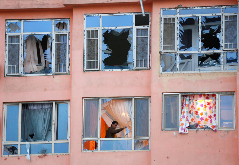 Image: An Afghan man removes glasses from his apartment at the site of a suicide attack in Kabul, Afghanistan