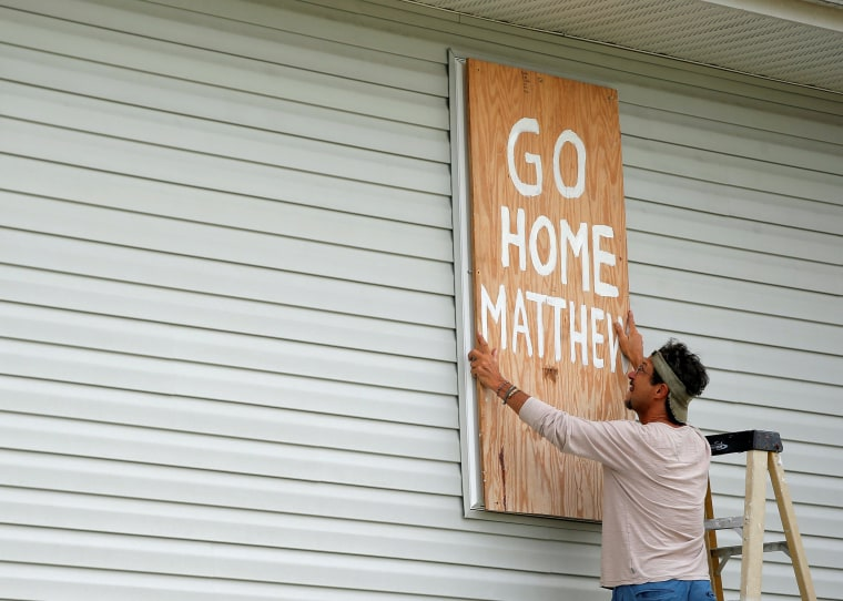 Image: Homeowner Don Appell prepares to board up one of the windows at his home ahead of Hurricane Matthew in Cherry Grove