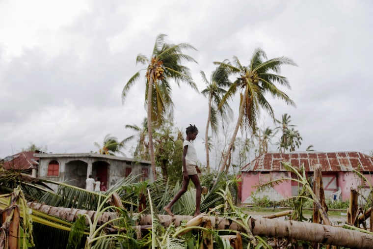 Image: A girl walks on a tree damaged by Hurricane Matthew in Les Cayes