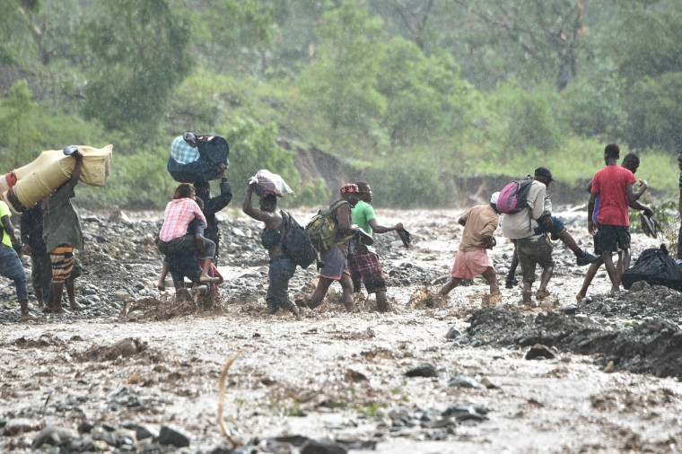 Image: Haitian people cross the river La Digue in Petit Goave