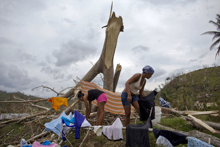 Image: People lay their clothes out to dry on a tree broken by the winds of Hurricane Matthew