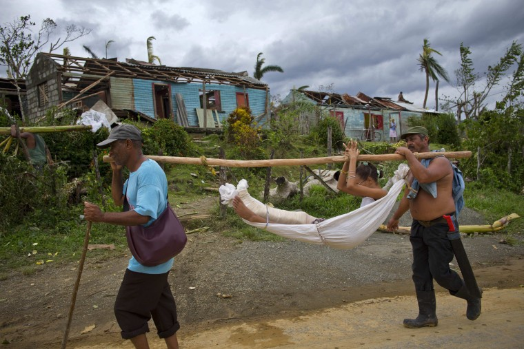 Image: A young woman who was in hospital with a broken leg is carried by two men in a hammock back to her home in Baracoa