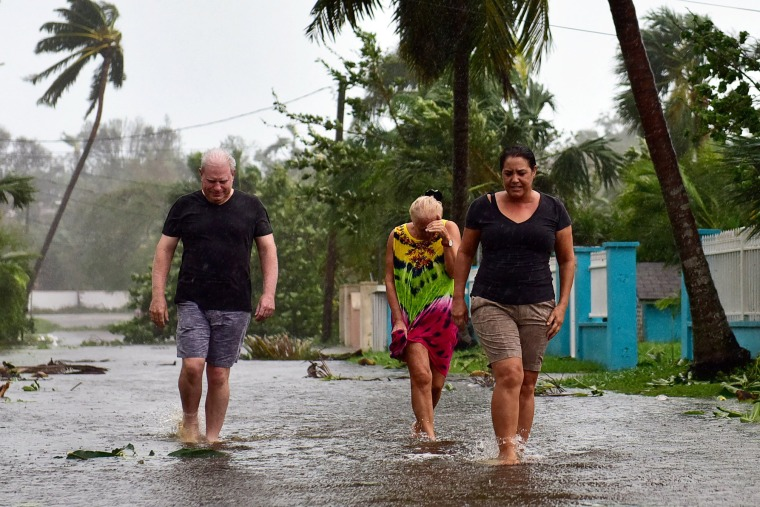 Image: Residents of Grove West walk through flooded streets in the aftermath of Hurricane Matthew in Nassau