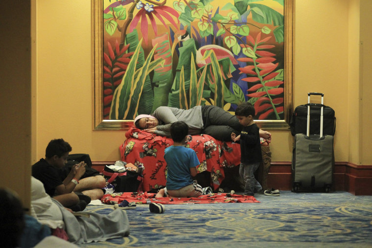 Image: Guests rest in a hallway at the Atlantis Paradise Island hotel