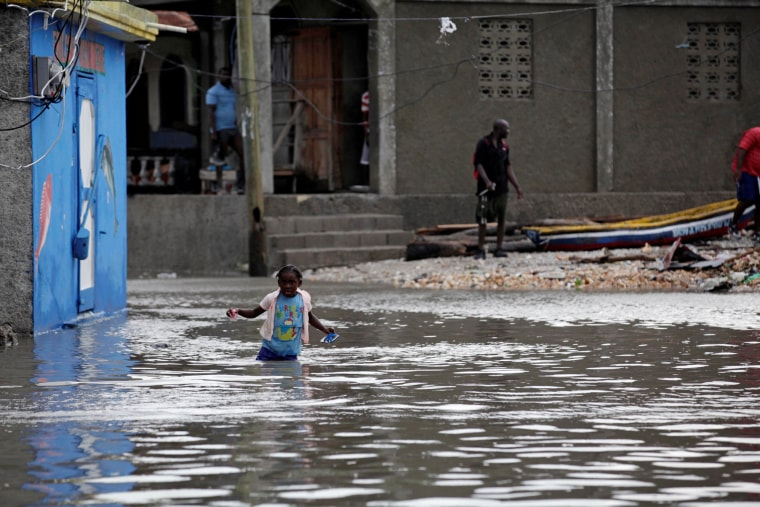Image: A girl walks in a flooded area after Hurricane Matthew in Les Cayes