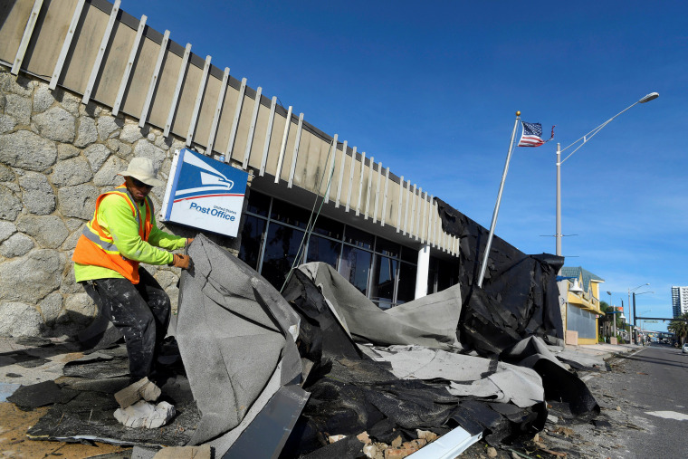 Image: Jordan Mays removes the roof that blew off of a U.S. Post Office location in the aftermath of Hurricane Matthew in Daytona Beach