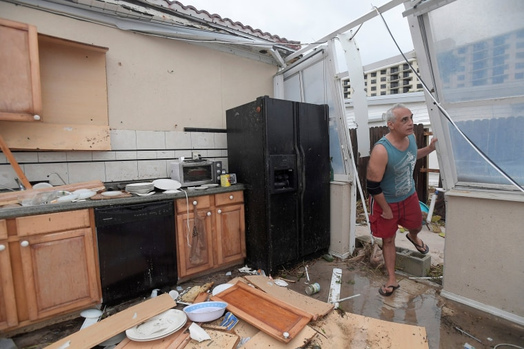 Image: Homeowner Joe Lovece surveys the damage to the kitchen at the back of his oceanfront home after the eye of Hurricane Matthew passed Ormond Beach