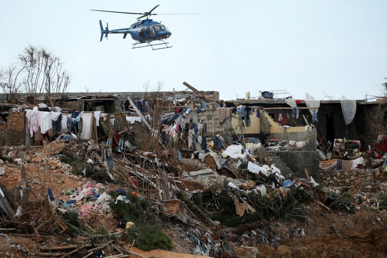 Image: A helicopter flies over destroyed houses after Hurricane Matthew passes Jeremie