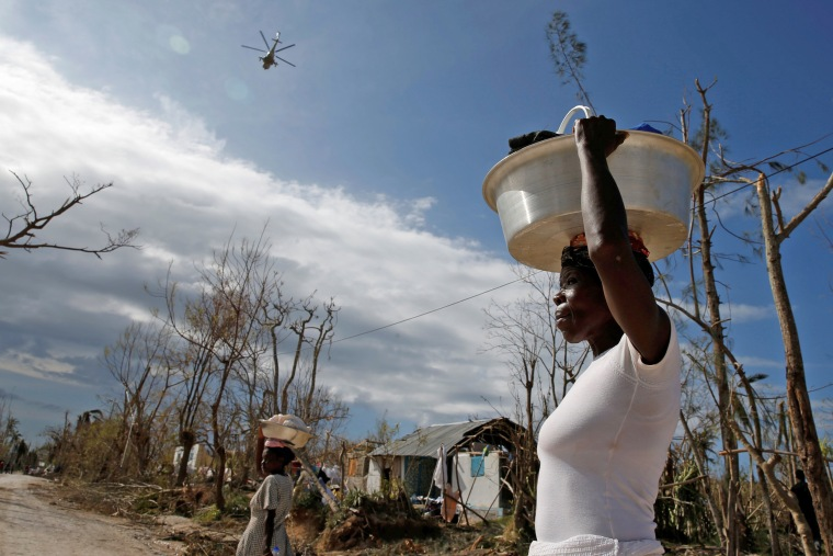 Image: Women carry their belongings as a helicopter flies in the sky, after Hurricane Matthew hit Jeremie