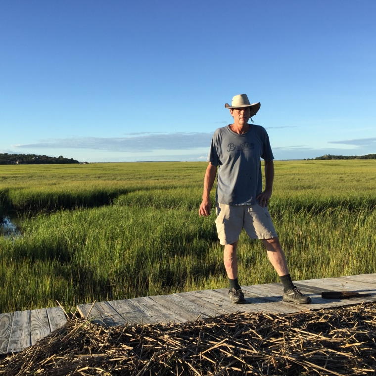 """Kevin Mellogy of Little Piney Island in Fernandina Beach, Florida, stands on a section of his dock on Oct. 8 that was blown three quarters of a mile away from his house by Hurricane Matthew. \""""I spotted it with my telescope,\"""" he says, \""""Some of it probably washed back out. God knows where it is.\"""""""