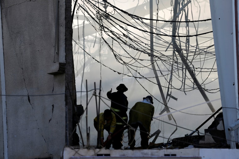 Image: Fire fighters extinguish fires after what witnesses said was an airstrike by Saudi-led coalition aircraft on mourners at a hall in Sanaa