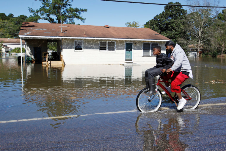 Image: Residents ride their bicycle past a flooded house after Hurricane Matthew hit Lumberton