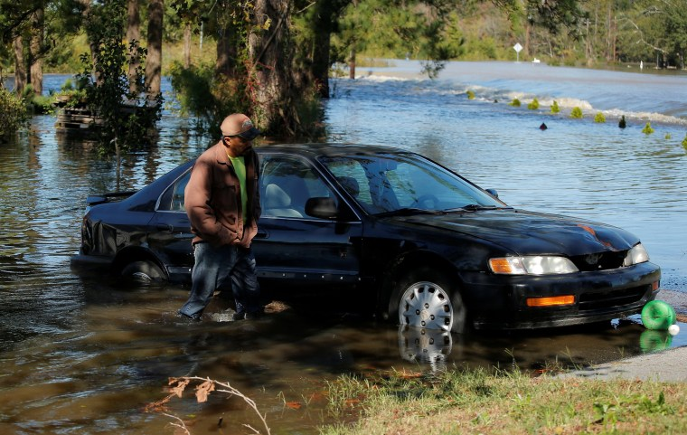 Image: A man walks through flooded waters near his home after Hurricane Matthew in Lumberton