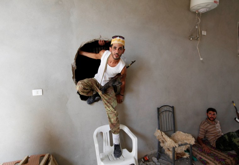 Image: A fighter from Libyan forces allied with the U.N.-backed government climbs out of a hole during a fight with Islamic State in neighbourhood Number Three in Sirte