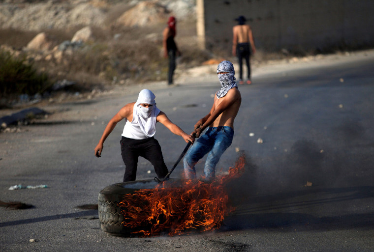 Image: Palestinian protesters drag a burning tyre during clashes with Israeli troops in the West Bank town of Al-Ram